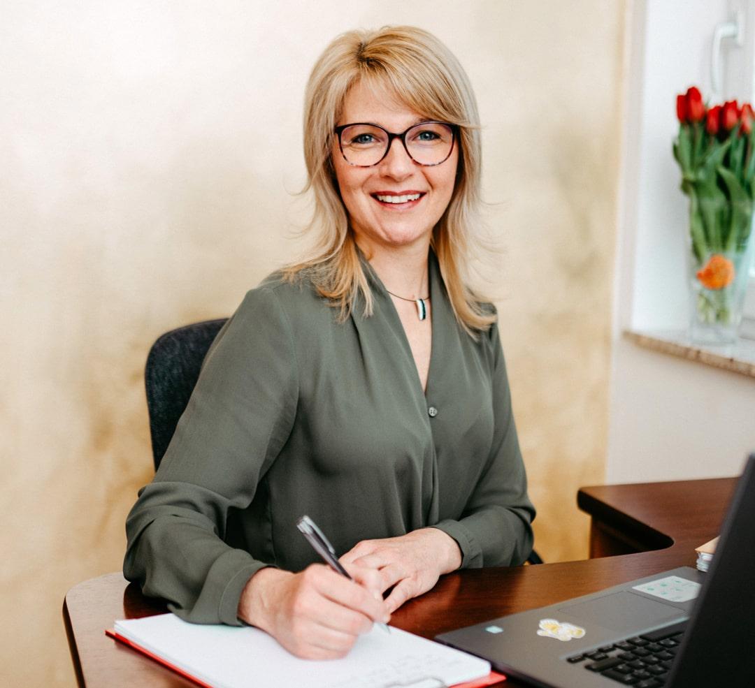 Christine Furlan-Stichauner sitzt am Schreibtisch.